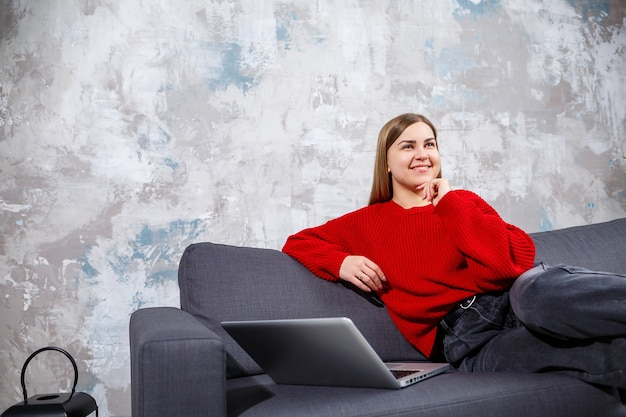 아늑한 집 내부의 소파에 앉아 현대적인 노트북 컴퓨터에서 원격으로 일하는 프리랜스 여성, 웹사이트에서 온라인 웨비나를 시청하는 경험 많은 여성. 검역 중 재택근무