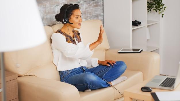 Женщина-фрилансер включает наушники во время видеозвонка, работая из дома.