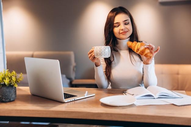 家に座っている間ラップトップを使用してフリーランスの女性。キッチンに座って、ラップトップで作業している若い女性。仕事中にお茶のコーヒーを飲むきれいな女性。