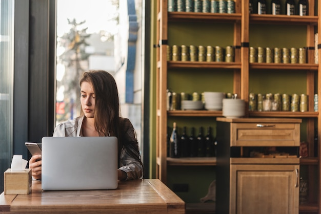 Freelance woman working with laptop in coffee shop