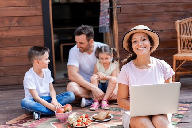 Freelance woman working with laptop sitting on porch during family vacation enjoying wifi and 5g
