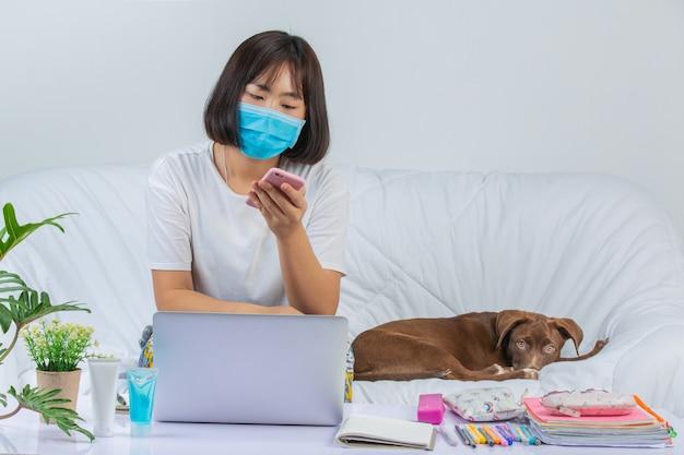 Внештатный, работа на дому - молодая женщина работает рядом с собакой на диване у себя дома.