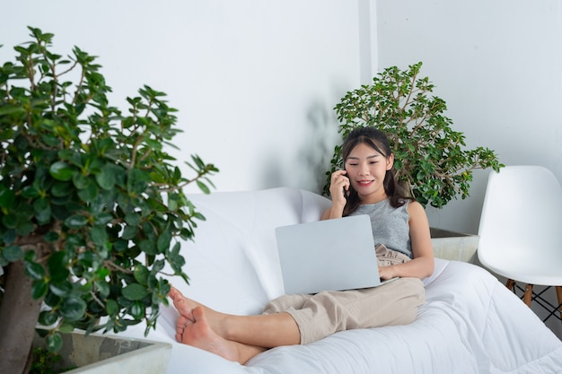 Внештатный, работающий из дома - молодая женщина пользуется телефоном, работая в гостиной.