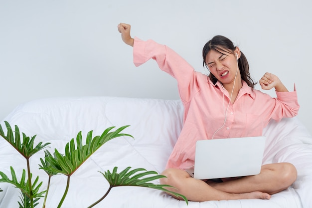 Freelance, working at home - young woman is stretching after finished the work on sofa, she is listening to music.