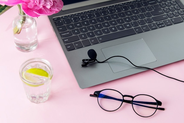 Freelance workspace. laptop, microphone, glasses, water with lemon on a pink wall. podcast recording concept.