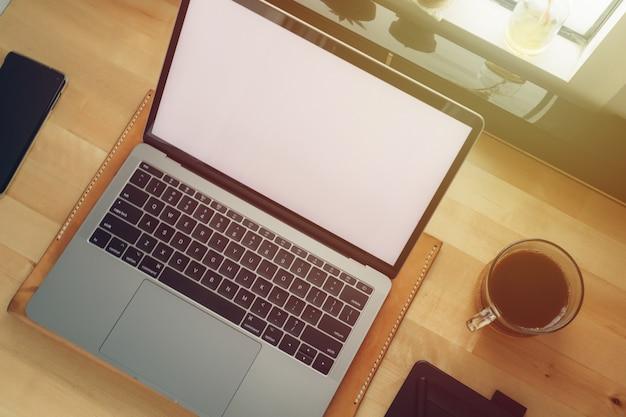 Freelance workspace laptop on wooden desk with window light.