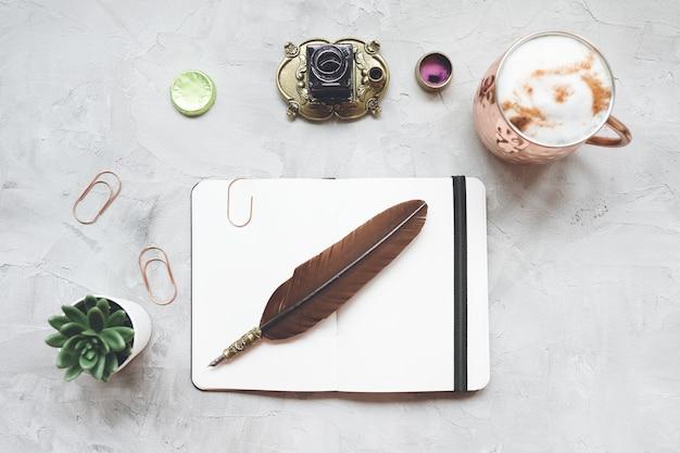 커피, 노트북, 깃털, 잉크, 즙이 많은 식물이있는 프리랜서 작가 사무실 책상 작업 공간