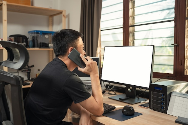 Freelance young asian man calling with cell phone and empty display, storage box at wooden desk on window side in house