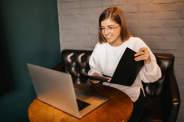 Внештатный. молодая счастливая кавказская женщина с компьтер-книжкой. записывает информацию в блокнот, обучение в интернете