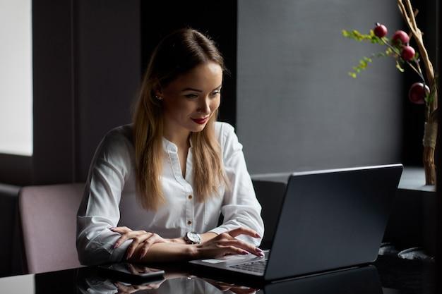 仕事でフリーランサー。若いブロンドの笑顔のかわいい女性起業家がスタイリッシュなコーヒーショップでノートパソコンでの作業します。