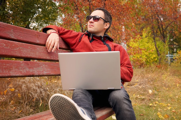 Freelancer in autumn park. magazine editor revising new article received by email. man surfing web on a laptop connected to wifi. student preparing for the exams outdoors by using a portable computer.