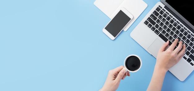 커피와 함께 깨끗한 밝은 파란색 책상에서 휴식을 취하기 위해 마시는 프리랜서 블로그 작가 여자, 집 개념에서 작동