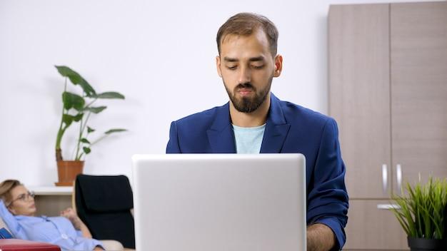 집에서 노트북 컴퓨터 작업을 하는 프리랜서 사업가와 그의 아내가 뒤에 있다