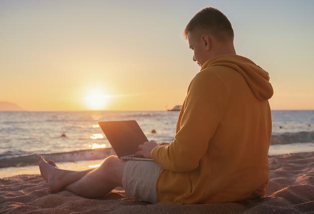 Фрилансер у моря работает с ноутбуком на рассвете