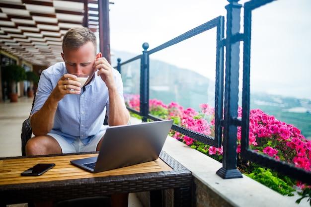 프리랜서 개념. 성공적인 젊은 남자, 사업가 랩톱 컴퓨터에서 작업, 커피를 마시고 전화로 이야기 테라스에 앉아.