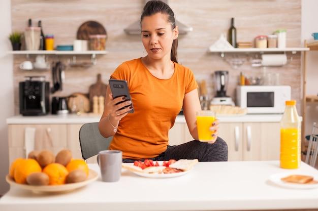Фрилансер пьет свежий апельсиновый сок по утрам, проверяя электронную почту на смартфоне