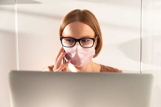 Freelancer in glasses wearing medical protective mask, talking on smartphone, work on laptop