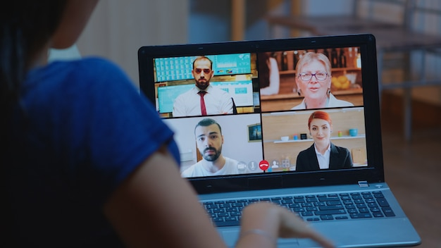 Freelancer having video conference at night with team sitting on couch using laptop. remote worker discussing at online meeting, consulting with colleagues using videocall and webcam working from home