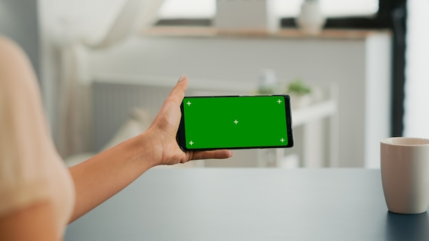 Freelancer holding smartphone with mock up green screen chroma key in horizontal position. business woman searching online information using isolated device sitting on office desk