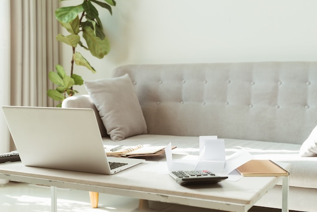 Ноутбук фрилансера на столе с калькулятором и блокнотом с принадлежностями на ярком домашнем диване в гостиной