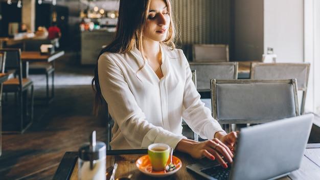 Образ жизни фрилансера. работа онлайн. расслабленная деловая женщина, работающая на ноутбуке в кафе.