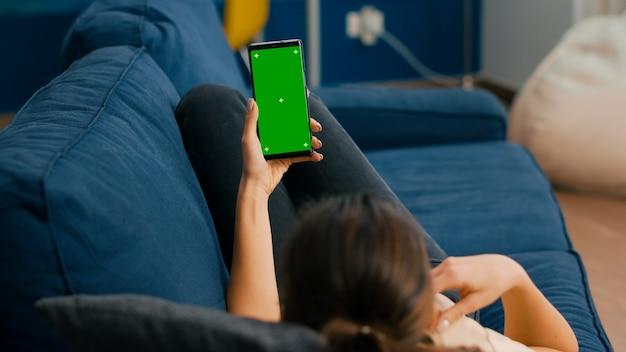 프리랜서는 스마트폰에서 온라인 화상 통화를 하는 동안 소파에 누워 수직 모드에서 녹색 화면 크로마 키를 조롱합니다. 소셜 네트워크 탐색을 위해 격리된 터치스크린 장치를 사용하는 여성