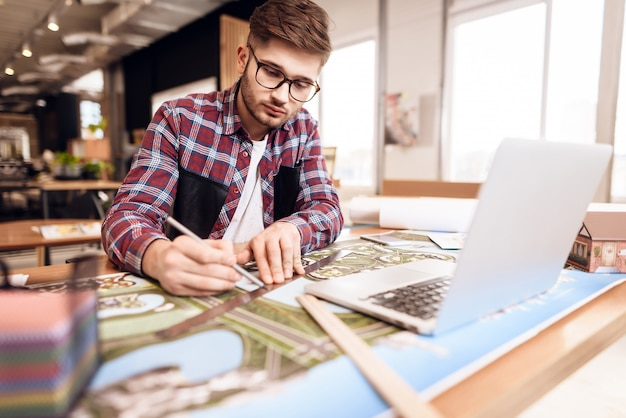 Freelancer man drawing on plan at laptop sitting at desk.