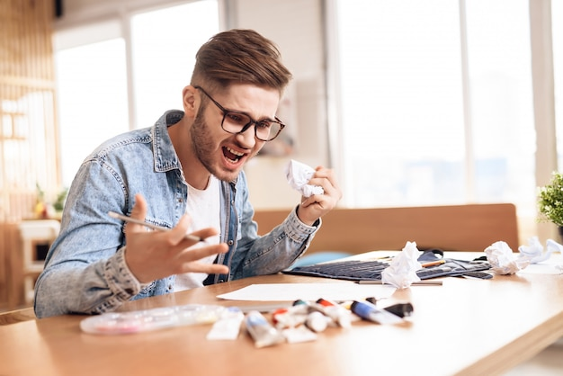 Фрилансер человек расстроен на рисунок, сидя за столом.