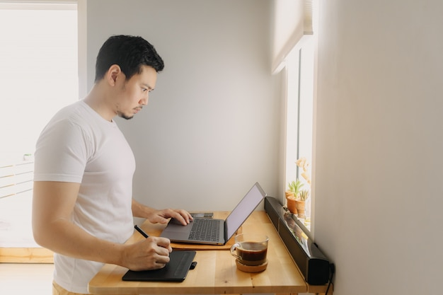 Freelancer man is working on his laptop in his apartment. concept of freelance creative works.