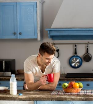 Freelancer man in the kitchen in pyjamas.