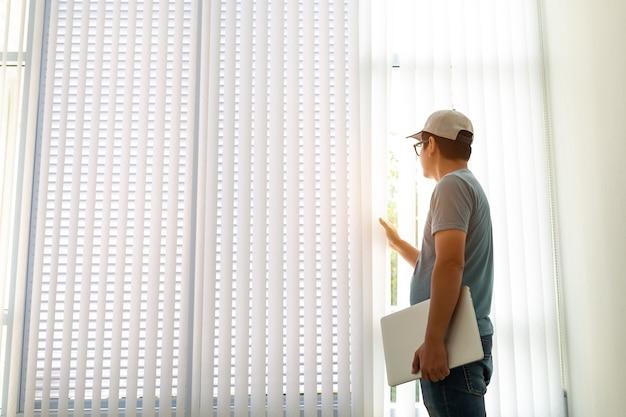 Freelancer man laptop computerを使用して新しい仕事を作成するためのアイデアを探しているウィンドウのそばに待機します。