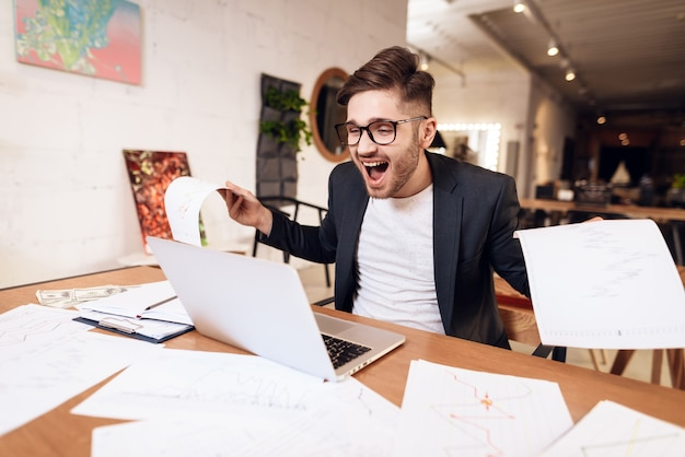 Freelancer man looking happy at laptop sitting at desk.