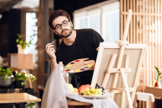 Freelancer man painting with brush standing behind easel.