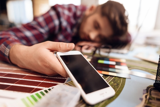 Freelancer man sleeping at laptop sitting at desk.