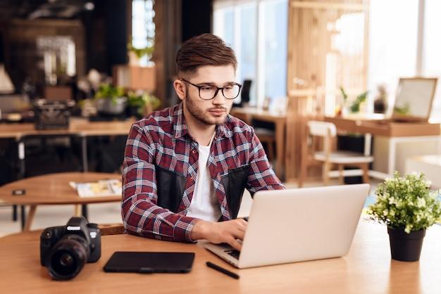 Freelancer man typing at laptop sitting at desk.