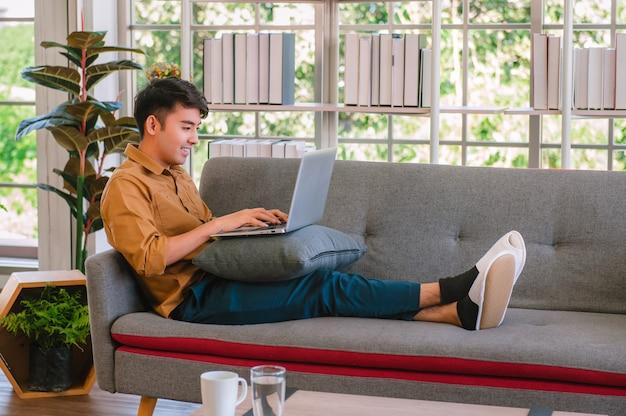 ソファで自宅で作業するためにラップトップを使用してフリーランサーの男