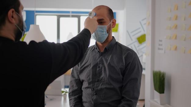 コロナウイルスの感染を防ぐために体温計を使用して温度をチェックしながら、covid19に対する保護マスクを着用しているフリーランサーの男性。世界的大流行時に予防策を講じている企業