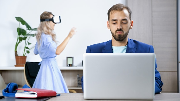아내가 가상 현실 헤드셋으로 비디오 게임을 하는 동안 집에서 컴퓨터로 일하는 프리랜서 남자
