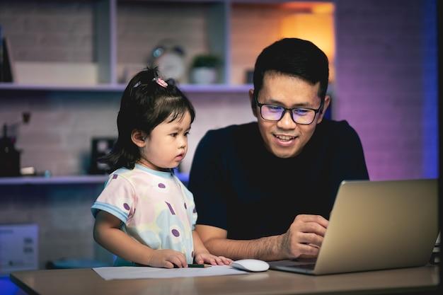 Фрилансер работает с ноутбуком на столе и разговаривает со своей дочерью