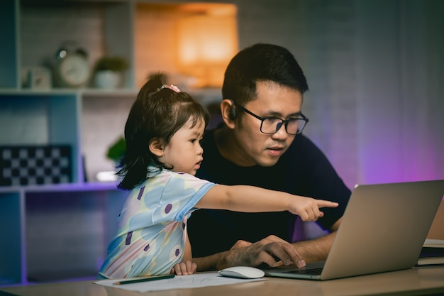 Freelancer man working with laptop on the table and talking with his daughter
