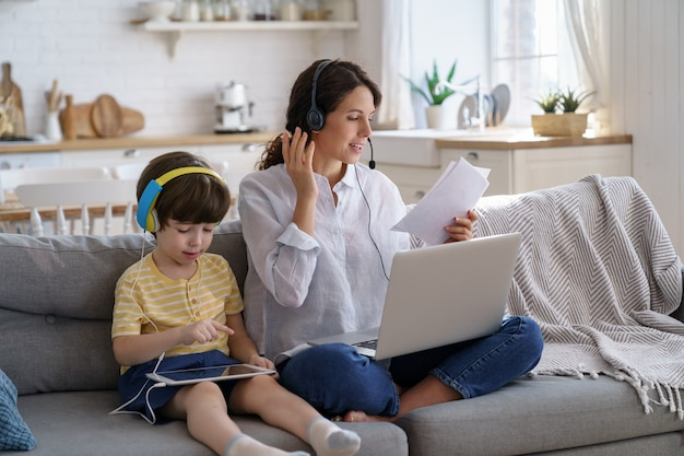 Freelancer mom sitting on sofa at home during lockdown working on laptop and kid playing at tablet