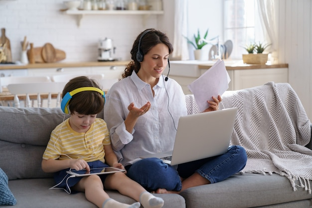 Freelancer mom sitting on sofa at home office during lockdown work on laptop, kid playing at tablet