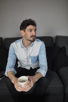 Фрилансер отдыхает с чашкой кофе на диване, думая