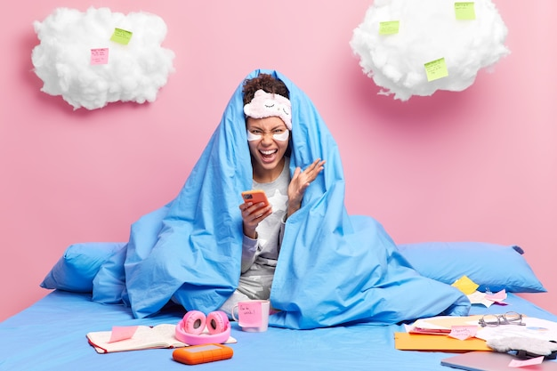 Freelancer screams loudly uses mobile phone coned with blanket undergoes beauty procedures stays and works from bed makes notes onn sticky notes isolated on pink wall