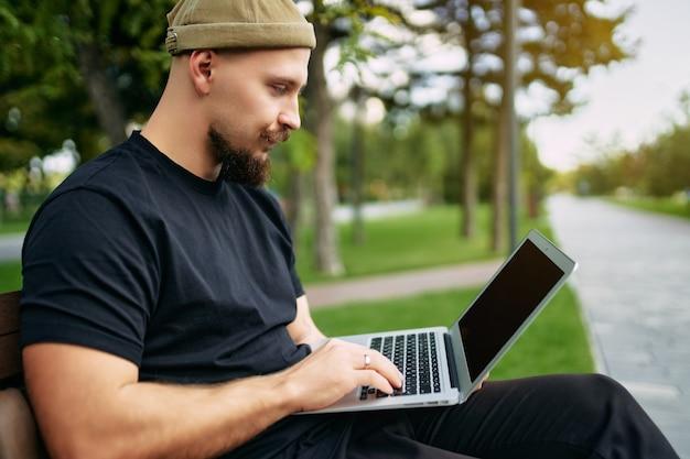 프리랜서는 도시 공원에 앉아 노트북 블로거 힙스터 여행자 젊은 세련된 남자에게 타이핑을 하고 있다