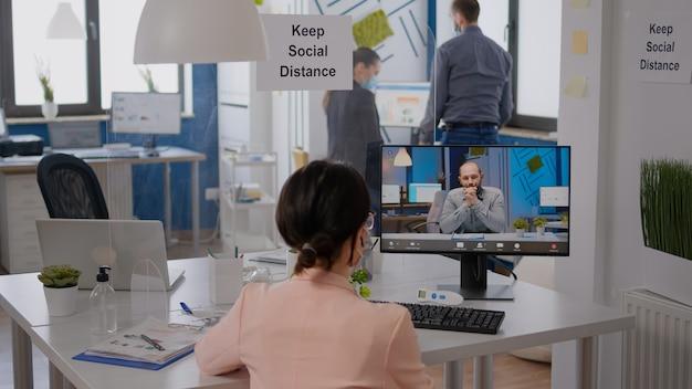 Фрилансер сидит за письменным столом в новом обычном офисе компании, в защитной маске во время виртуальной видеоконференции. коллеги, работающие за компьютером во время пандемии коронавируса
