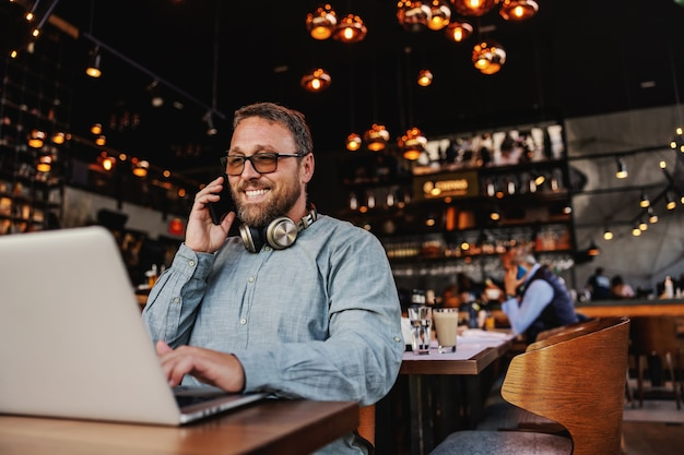Freelancer sitting in a bar, having phone conversation with employer and using laptop for work.