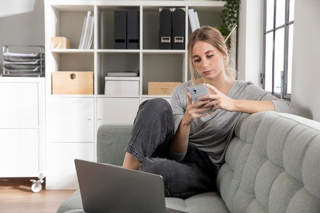 Freelancer sitting on couch with phone