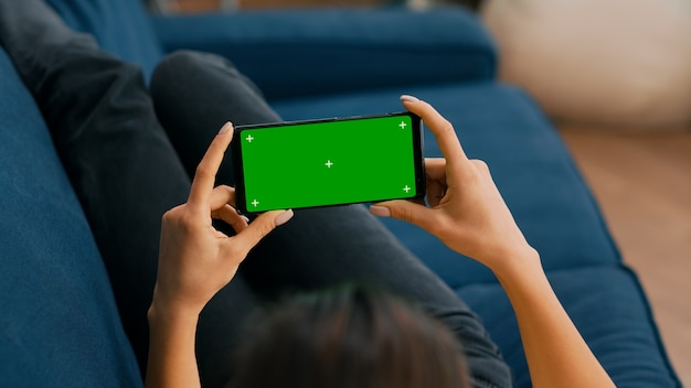 Freelancer sitting on sofa while looking at movies using phone in horizontal mode with mock up green screen chroma key display. woman using isolated touchscreen device for social networks browsing
