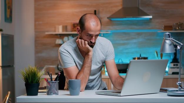 프리랜서는 집 부엌에 앉아 노트북을 보며 잠이 드는 과중한 업무로 스트레스를 받았습니다. 지친 원격 직원이 의자에서 낮잠을 자고 일어나 현대 기술 네트워크를 사용하여 pc에서 작업